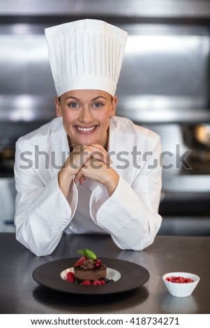 Portrait of happy female chef with hands on chin in commercial kitchen - stock photo