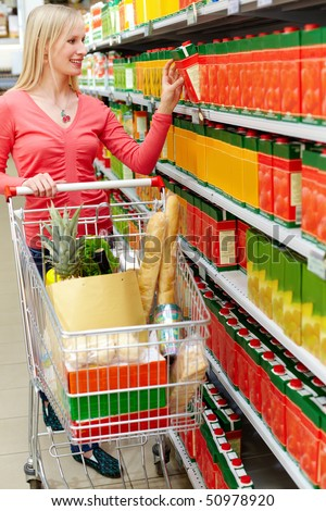Portrait of happy female choosing pack of juice in supermarket - stock photo