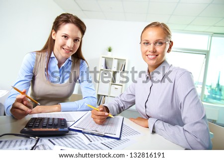 Portrait of happy female colleagues accounting in office - stock photo