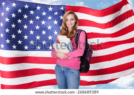 Portrait of happy female college student with backpack and books standing against white background