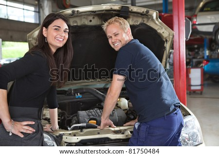 Portrait of happy female customer and mechanic in garage - stock photo