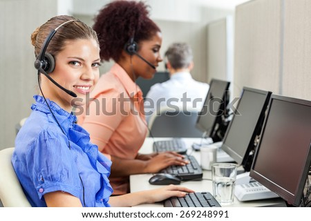 Portrait of happy female customer service agent using computer with colleagues in background at office