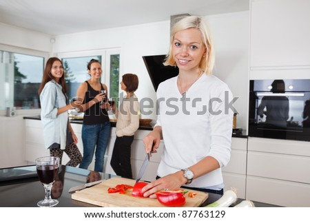 Portrait of happy female cutting vegetables while friends having drink in background - stock photo