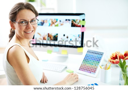 Portrait of happy female designer looking at camera at workplace - stock photo