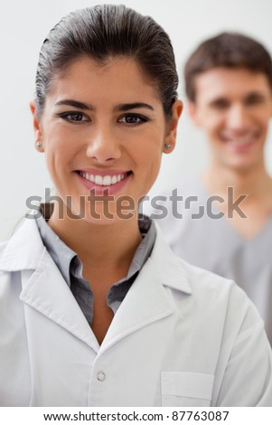 Portrait of happy female doctor with practitioner standing in background - stock photo