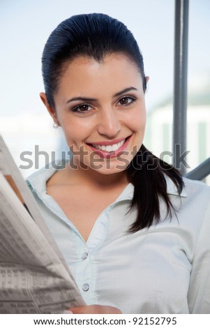 Portrait of happy female executive holding newspaper - stock photo