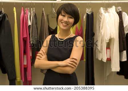 Portrait of happy Female fashion designer standing arms crossed - stock photo