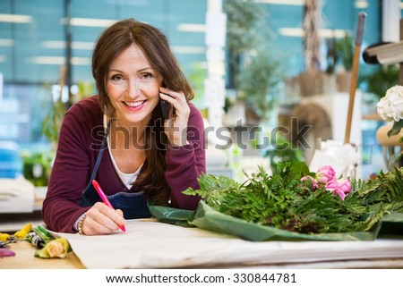 Portrait of happy female florist using mobile phone while writing on paper in flower shop - stock photo