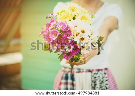 Portrait of happy female florist with bunch of colorful flower looking at camera