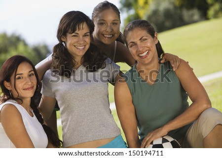 Portrait of happy female friends with soccer ball at park - stock photo