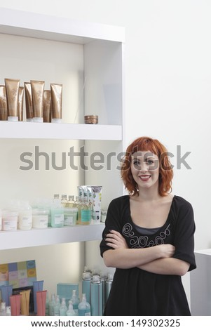 Portrait of happy female hairdresser standing arms crossed against shelves at salon - stock photo