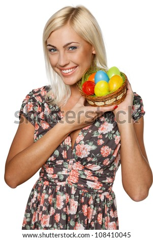 Portrait of happy female holding basket with Easter eggs, isolated on white background