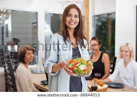Portrait of happy female holding bowl of vegetables while her friends sitting in background - stock photo