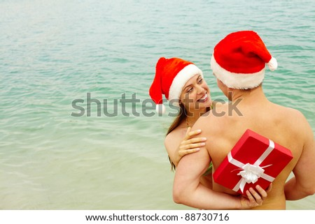 Portrait of happy female in Santa cap embracing her husband while he hiding gift behind his back - stock photo