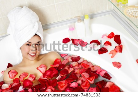 Portrait of happy female in water surrounded by rose petals