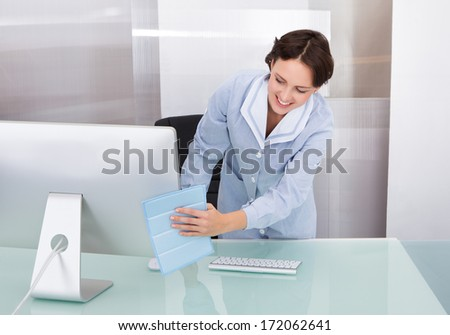 Portrait Of Happy Female Janitor Cleaning Desk At Office - stock photo