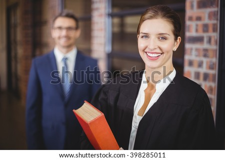 Portrait of happy female lawyer with businessman standing in background - stock photo