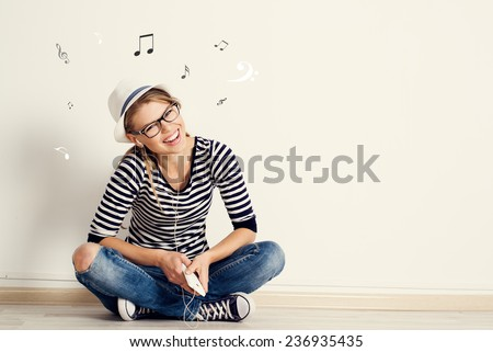 Portrait of happy female listening musical composition in earphones with sheet music and clef drawn on the wall. Young pretty Caucasian woman sitting on wooden floor in her house.  - stock photo