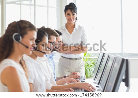 Portrait of happy female manager with business staff working in a call center - stock photo