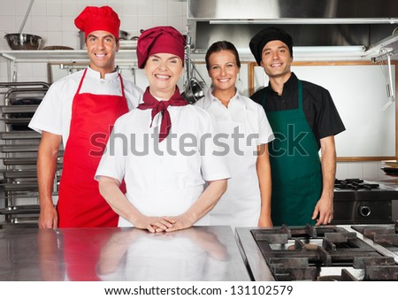 Portrait of happy female mature chef with colleagues in commercial kitchen