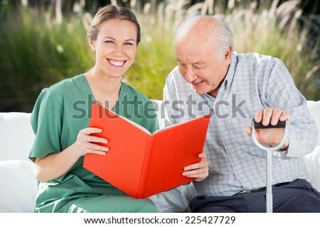 Portrait of happy female nurse reading book for senior man at nursing home - stock photo