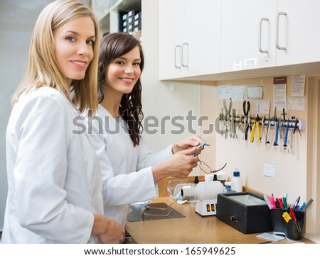 Portrait of happy female opticians repairing glasses in workshop - stock photo