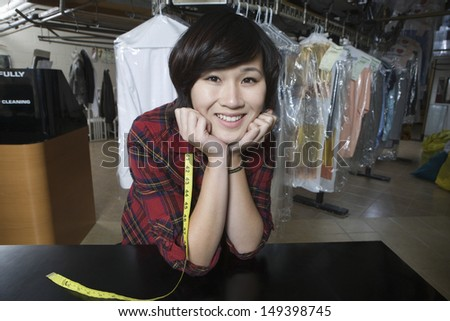 Portrait of happy female owner with hands on chin in laundry - stock photo