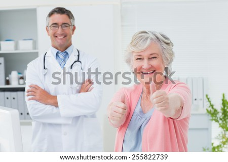 Portrait of happy female patient showing thumbs up sign while standing with doctor in clinic - stock photo