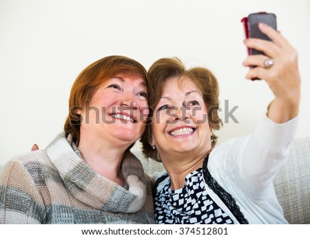 Portrait of happy female pensioners making selfie on phone and smiling at home - stock photo