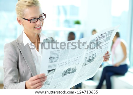 Portrait of happy female reading newspaper in working environment - stock photo