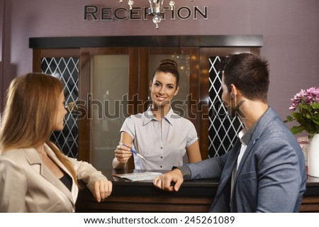 Portrait of happy female receptionist giving information to young couple. - stock photo