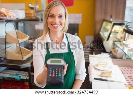 Portrait of happy female shop owner holding credit card reader in bakery - stock photo