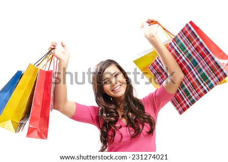 Portrait of happy female shopaholic with several paper bags looking at camera