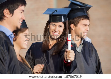 Portrait of happy female student showing diploma while standing with friends at college - stock photo