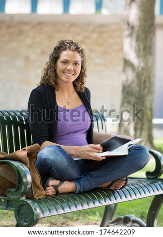 Portrait of happy female student studying on bench at university campus - stock photo