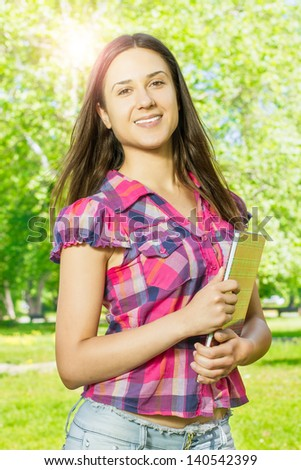 Portrait of happy female student with book in the park..