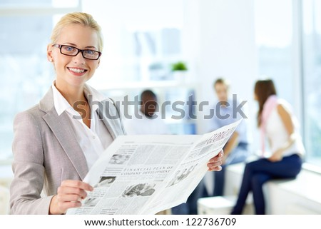 Portrait of happy female with newspaper looking at camera in working environment - stock photo