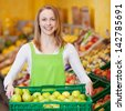 Portrait of happy female worker carrying apple's crate in grocery store - stock photo