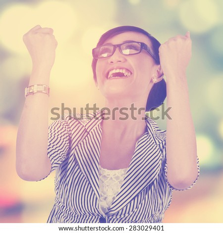 Portrait of happy female worker celebrating her victory with a bokeh background - stock photo