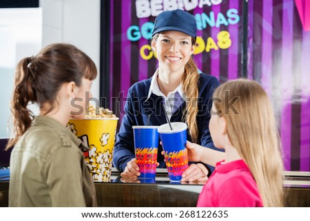 Portrait of happy female worker selling snacks to girls at cinema concession stand - stock photo