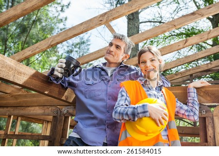 Portrait of happy female worker standing with colleague holding coffee mug at construction site - stock photo