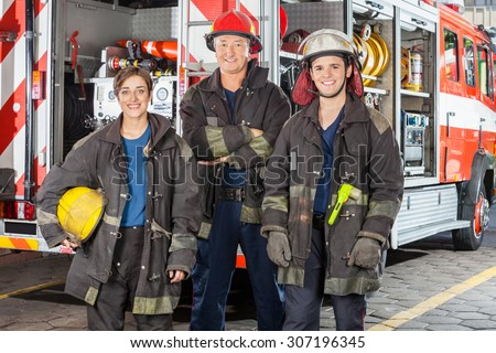 Portrait of happy firefighters standing together against truck at fire station - stock photo