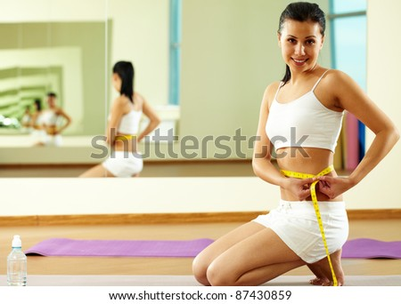 Portrait of happy fit female measuring her waist - stock photo