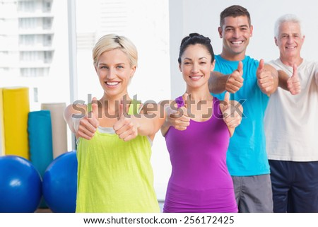Portrait of happy fit people gesturing thumbs up at gym - stock photo