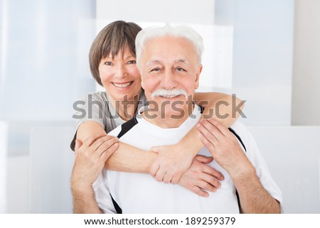 Portrait of happy fit senior couple embracing at gym - stock photo