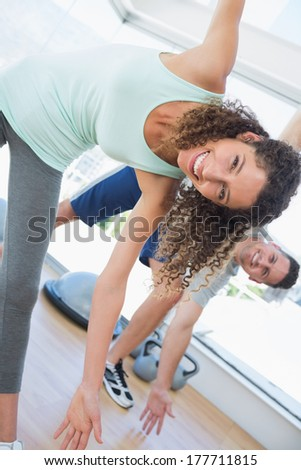 Portrait of happy fit woman stretching in health club - stock photo