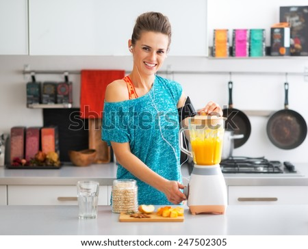 Portrait of happy fitness young woman making pumpkin smoothie in kitchen - stock photo