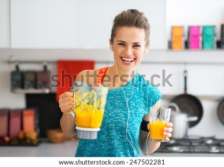 Portrait of happy fitness young woman with pumpkin smoothie in kitchen - stock photo