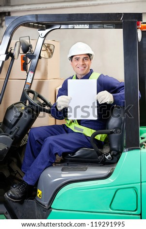 Portrait of happy forklift driver displaying blank placard - stock photo
