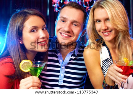 Portrait of happy friends cheering up and looking at camera at party - stock photo